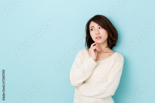 Poster attractive asian woman thinking on blue background
