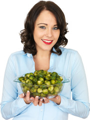 Young Woman Holding a Bowl of Brussels Sprouts