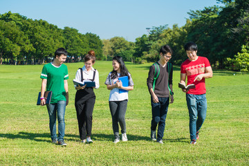 Happy group of students walking and talking at the park