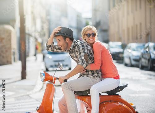 glamorous couple on a scooter in the street