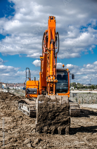 Poster Big orange excavator against the blue sky