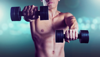 Man exercises with dumbbells on blue glow background