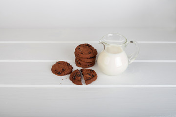 glass jug with milk and chocolate chip cookies