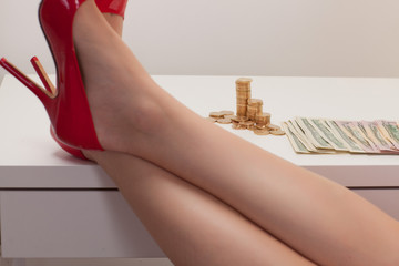 women's legs on  table and number of banknotes