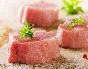 Raw beef with herbs on a wooden background.