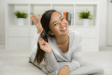 Portrait of a smiling asian teenager relaxing at home