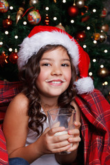 Cute little girl drinking milk in Santa hat