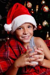 Cute little boy drinking milk in Santa hat
