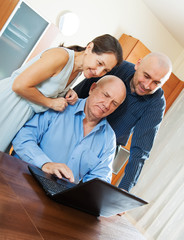 Three smiling people with laptop