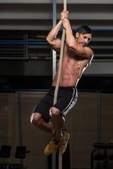 Young Man Climbing A Rope