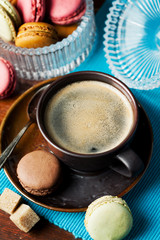 Cup of coffee and macaroons on wooden table, toned