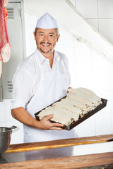 Butcher Carrying Tray Filled With Dredge Chicken