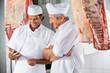 Leinwanddruck Bild - Butchers Looking At Digital Tablet In Butchery