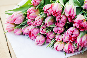 Bunch of beautiful pink tulips on wooden table