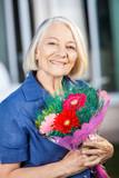 Happy Senior Woman Holding Bouquet At Nursing Home