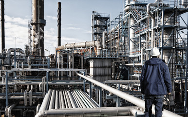 lonely worker standing in front of giant oil refinery