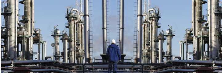 industry worker in front of giant refinery installation