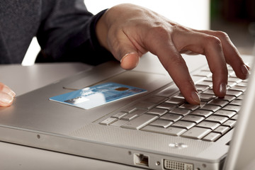 Credit card on laptop, and female hand typing on the keyboard