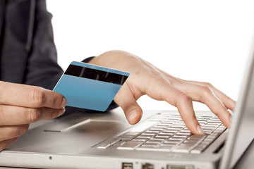 Female hands holding  a credit card and typing on the keyboard