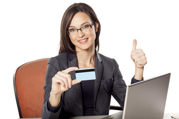 smiling businesswoman holding credit card and showing thumbs up