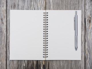 Blank page of book paper with pen on wooden background.