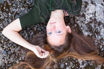 Young cute girl with her hair lying on a stone background.