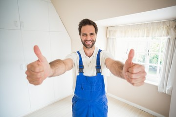 Handyman smiling at camera showing thumbs up