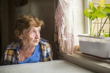 Old woman sitting alone near the window in his house.