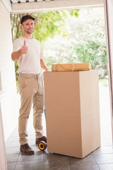 Delivery man with trolley of boxes giving thumbs up