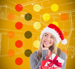 Composite image of festive blonde holding christmas gift and bag