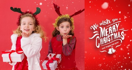 Composite image of festive little girls holding gifts