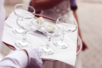 Waiter four glasses of champagne on table