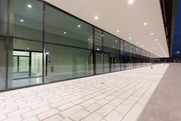 Illuminated pedestrian passage perspective along glass building