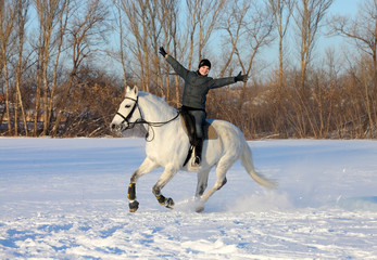 Young rider on a galloping horse is happy winter day