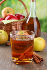Apple cider in glass and bottle, with cinnamon sticks and fresh