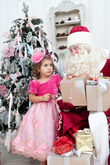 Little girl with a gift in hands and Santa Claus