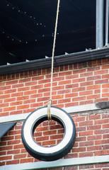 Tire Swing on Brick Wall