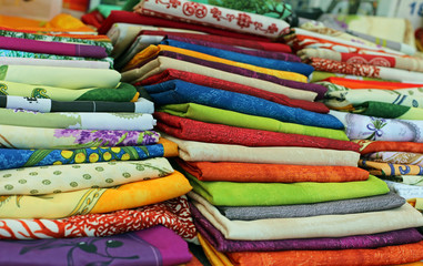 lots of colored cloth tablecloths for sale in the city market