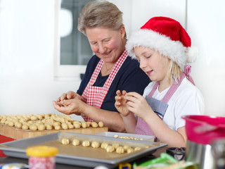 Grandmother and child baking biscuits
