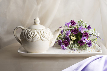 Teaspot, tray and violet flowers