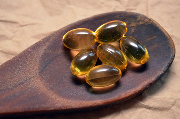 Fish oil capsules in wooden spoon