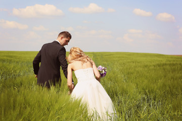 Bride and groom having fun on the fields