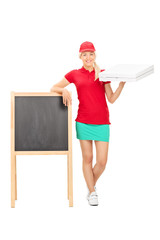 Pizza delivery girl standing by a blank blackboard