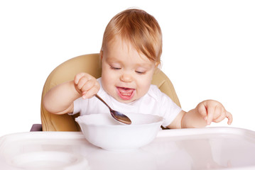 Baby eating with spoon. Isolated on white