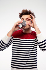 Casual man drinking coffe with closed eyes on gray background