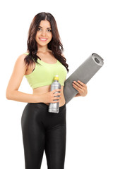 Female athlete holding an exercise mat