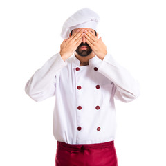 Chef covering his eyes over white background