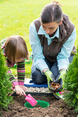 Mother and daughter planting tulip bulbs