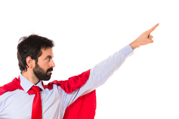 Businessman dressed like superhero pointing to the lateral