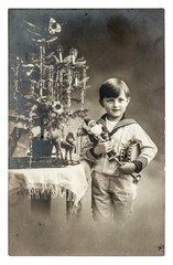 happy boy with christmas tree, gifts and vintage toys. antique p